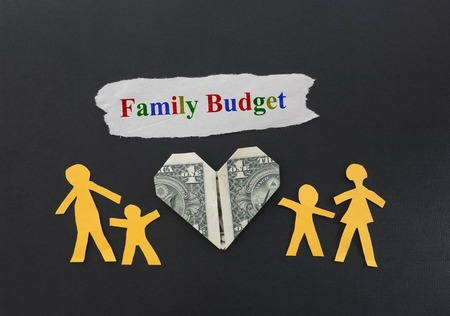 family budget: Paper cutout family of four with dollar heart and Family Budget text Stock Photo