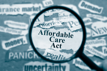 headlines: News headlines and magnifying glass with Affordable Care Act text