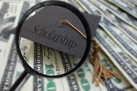 scholarship: Magnified graduation mortar board with Scholarship text, on money