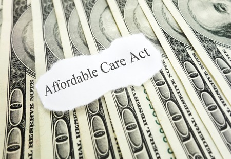 Affordable Care Act aka Obamacare and ACA, on cash photo