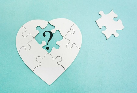 Heart shaped puzzle with question mark in missing piece