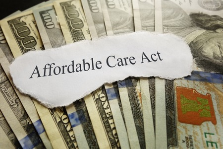 Affordable Care Act news headline on cash photo