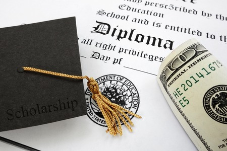 graduation cap with Scholarship text and money on a high school diploma