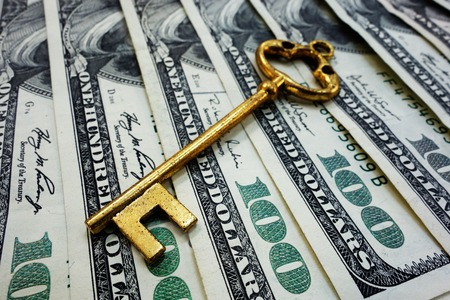 Gold antique key on hundred dollar bills