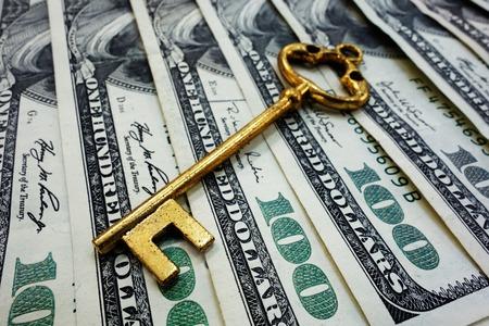 prosperidad: Llave antigua del oro en billetes de cien dólares Foto de archivo