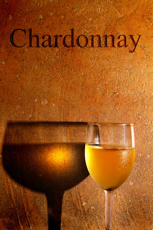 chardonnay: chilled glass of white wine against textured background with Chardonnay text Stock Photo