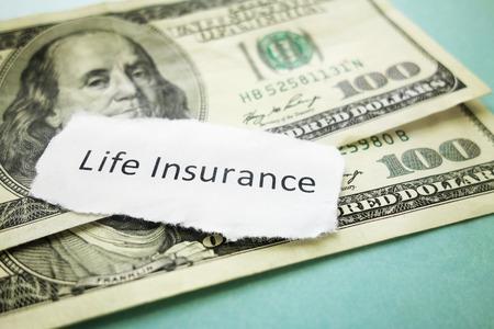 Paper scrap with Life Insurance text on cash Foto de archivo