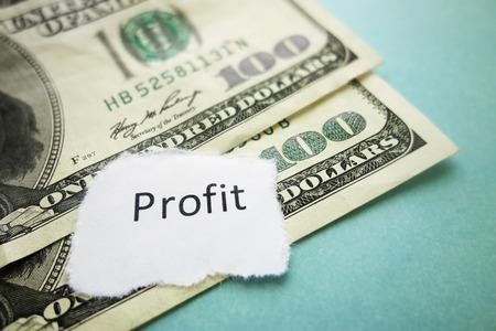 profiting: Profit newspaper headline on hundred dollar bills