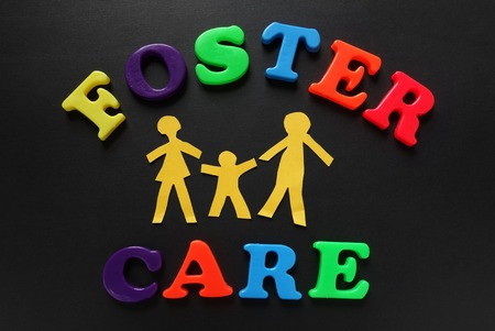 foster: Paper cutout people with Foster Care letters Stock Photo