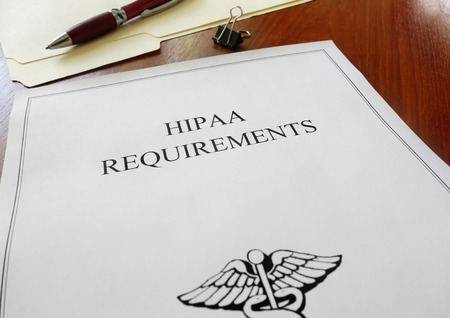 HIPAA healthcare requirements document with folder and pen