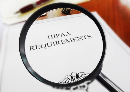 private information: HIPAA healthcare requirements document with magnifying glass Stock Photo