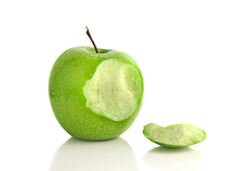 Green apple with bite taken out on white