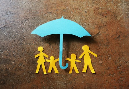 Paper family of four under a paper cutout umbrella Stockfoto