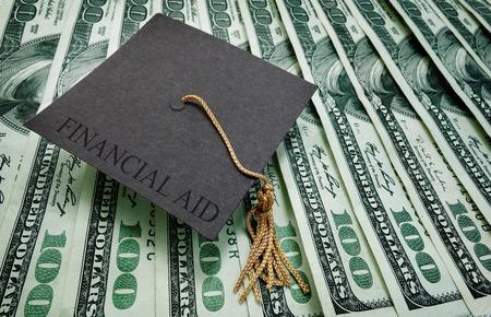 graduacion de universidad: casquillo de la graduación con el texto de ayuda financiera en una variedad de billetes de cien dólares