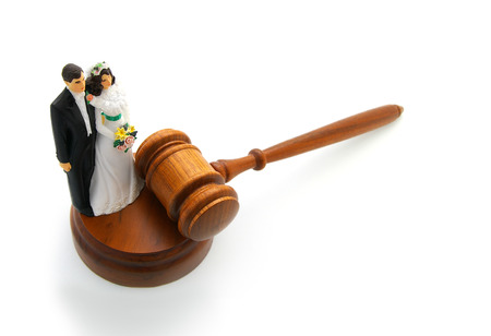 alimony: Plastic bride and groom with gavel on white   divorce concept