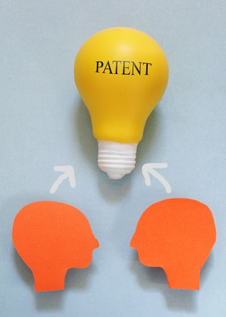 intellectual property: Two paper heads with a light bulb and Patent text Stock Photo