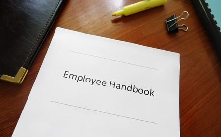 employee: Employee handbook document on an office desk