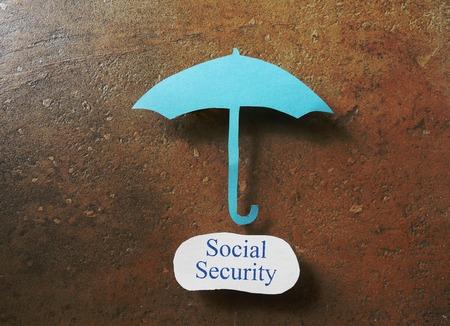 seguridad social: Paraguas de papel sobre el mensaje de la Seguridad Social Foto de archivo