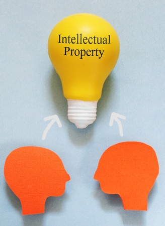 property rights: Two paper heads with a IP light bulb - Intellectual Property concept Stock Photo