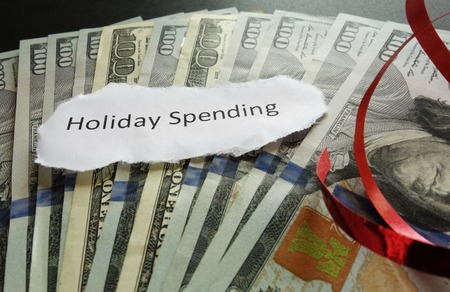 holiday budget: Holiday Spending note on cash, with red ribbon