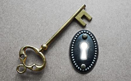 antique keyhole: antique gold key and ornate key hole with white Stock Photo