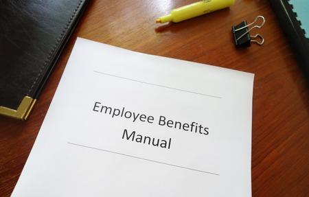empleados trabajando: Empleado Manual de Beneficios en un escritorio de oficina Foto de archivo