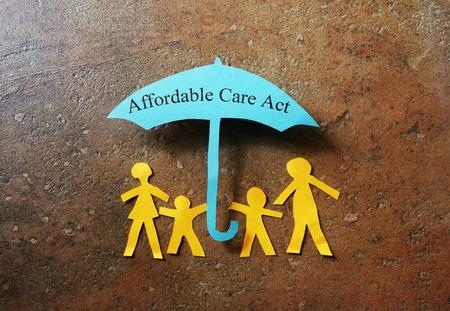 seguros: Familia de papel de cuatro bajo un paraguas de la Ley de Asistencia Asequible