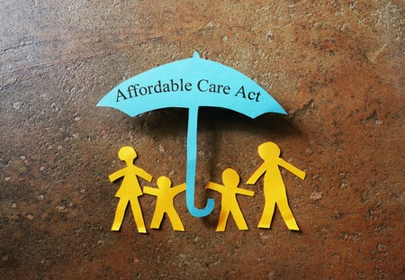 affordable: Paper family of four under a Affordable Care Act umbrella