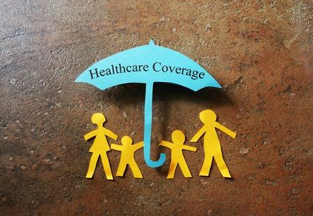 Papieren gezin van vier onder een gezondheidszorg Dekking paraplu Stockfoto