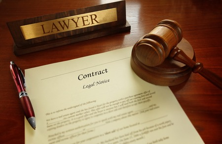 Legal contract with gavel and Lawyer name plate on a desk