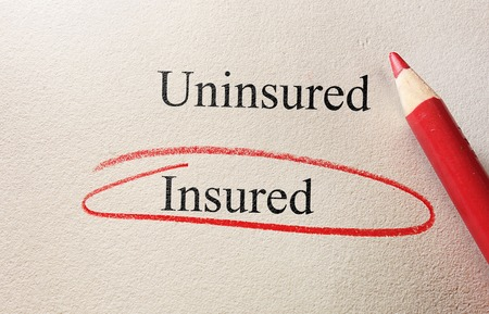 insured: Insured text circled with Uninsured text and pencil on textured paper Stock Photo