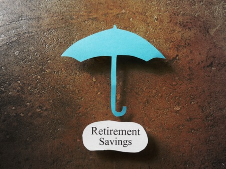 financial security: Paper umbrella over a Retirement Savings message