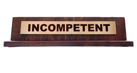 slacker: Incompetent wooden nameplate isolated on white