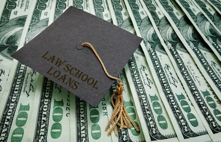 repay: Law School Loans graduation cap on assorted hundred dollar bills  student loan concept Stock Photo