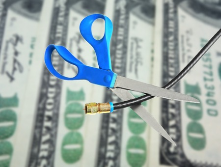 Scissors cutting through coax cable  cut the cable tv concept