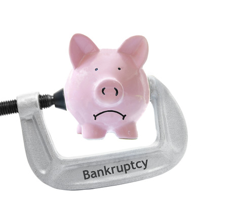 Sad piggy bank being squeezed in a Bankruptcy vice, on white Фото со стока