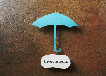 Paper umbrella over an Investments message  - safe investing concept