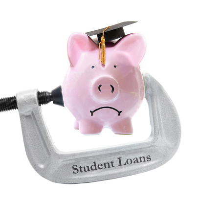 Frowning piggy bank wearing graduation cap being squeezed in a student loans vice on white