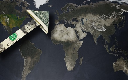 global currencies: Up arrow dollar over a world map  strong dollar or globalization concept