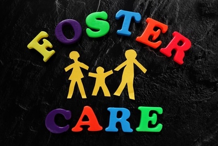foster: Paper cutout family with Foster Care letters