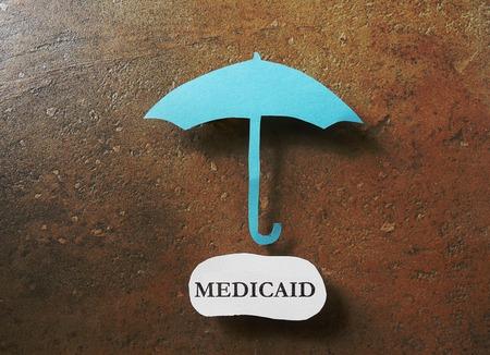 insure: Paper umbrella over a Medicaid message