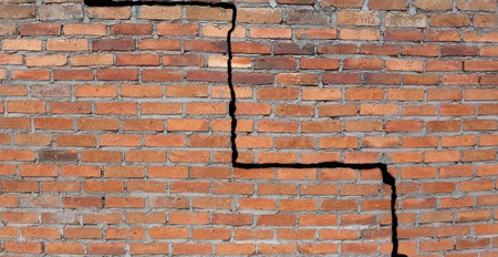 earthquake crack: Large crack in a brick wall building foundation Stock Photo