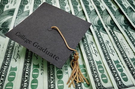 debt: College Graduate cap on assorted hundred dollar bills