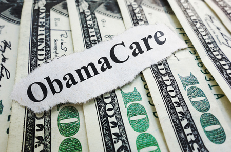 affordable: Obamacare newspaper headline on cash  Affordable Care Act cost concept
