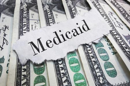 Medicaid torn newspaper headline on cash