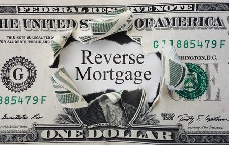 Gat in een dollarbiljet met omgekeerde hypotheek tekst Stockfoto