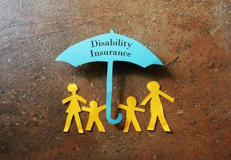 discapacidad: Familia de papel de cuatro bajo un documento de seguro de discapacidad paraguas