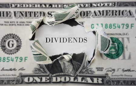 safe investment: Hole torn in a dollar bill with Dividends text