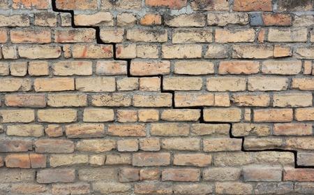 землетрясение: Старый кирпичный фундамент с трещиной в ступке Фото со стока