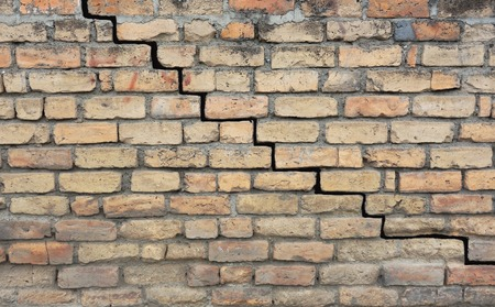 Old brick foundation with a crack in the mortar Stock Photo
